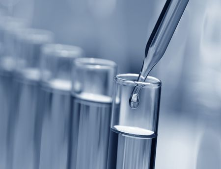 Pipette with drop of liquid over glass test tubes for an experiment in a science research lab photo