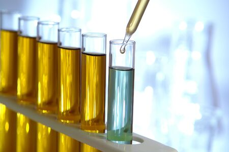 Pipette with drop of liquid over glass test tubes for an experiment in a science research lab Stock Photo - 4865573