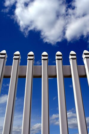 fence: White PVC yard picket fence over cloudy blue sky