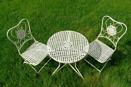 White shabby chic cast iron patio outdoor furniture set on grass lawn photo