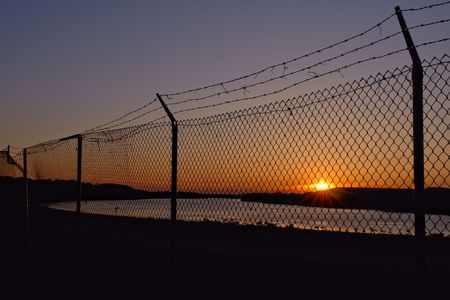 Barb wire chain link fence over a river at sunset