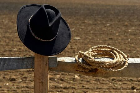 rodeo cowgirl: Western rodeo cowboy hat and rope on a wood post fence