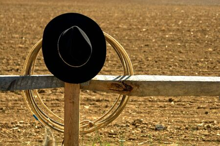 Western rodeo cowboy hat and lasso on a wood post fence