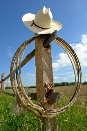 White straw cowboy hat and lasso on a wood post fence