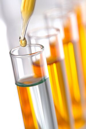yellow yellow lab: Pipette with drop of liquid over glass test tubes for an experiment in a science research lab Stock Photo