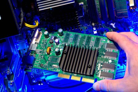 Technician hand holding a circuit board card inside a computer for repair or upgrade (all logos, trademark, markings, and identification numbers have been removed)