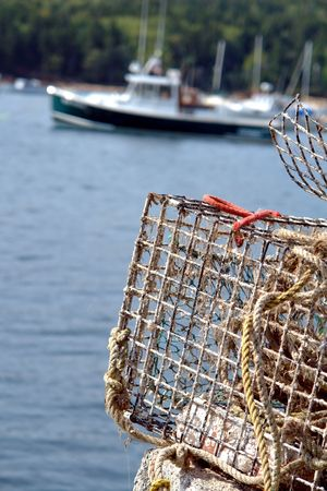 lobster boat: Lobster trap on a dock in a Maine fishing port with boat sailing by