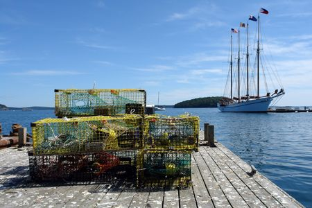 lobster pot: Lobster trap on a dock in a Maine fishing port with boat sailing by