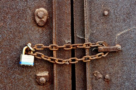 rusty chain: Chain and padlock on a closed old rusty steel door