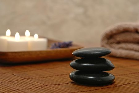 Symbolic meditative Zen inspired stone kern with burning candles and towel on a  bamboo mat in a spa photo