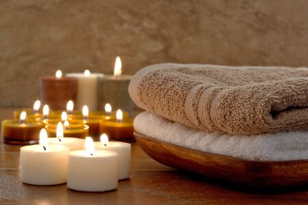 Bath towels and aromatherapy votive candles burning in a spa photo