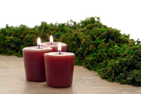 Aromatherapy organic candle burning with green dried moss in a spa photo