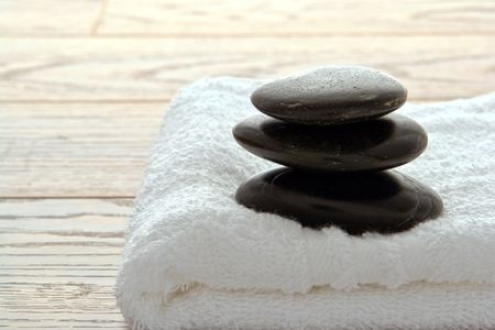 Black polished hot massage stone kern on a white towel in a spa Stock Photo