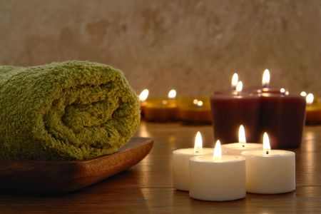 Bath towels and aromatherapy votive candles burning in a spa