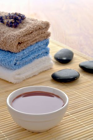 Hot massage oil in a bowl with black polished stones and stack of towels on a bamboo mat in a spa
