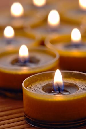 Aromatherapy organic votive candles burning on a bamboo mat in a spa