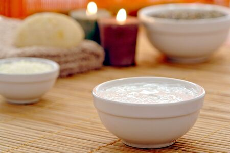 Facial treatment Cream in a bowl with aromatherapy products and burning candles in a spa