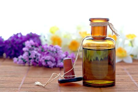 Aromatherapy scent essential oil extract amber bottle with flowers in a spa Foto de archivo