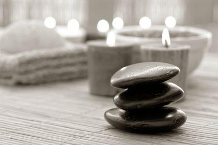 Zwart gepolijst hot massage Zen stenen kern met brandende kaarsen in een spa  Stockfoto