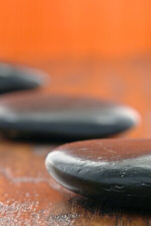 Black polished hot massage stones on wood surface in a spa Stock Photo