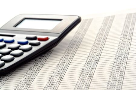 Financial figures spreadsheet with rows of numbers and calculator