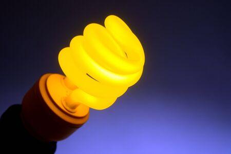Yellow color energy efficient CFL compact fluorescent light bulb lamp Stock fotó