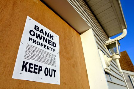 Real estate lender bank owned keep out  sign notice posted on a boarded up foreclosed house in foreclosure (fictitious document)