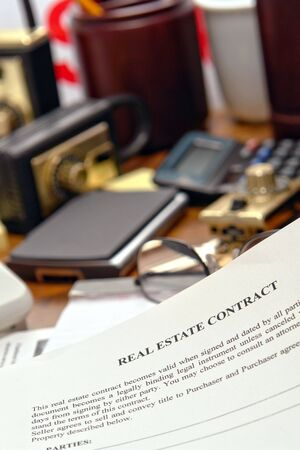 lockbox: Real estate contract document on busy Realtor desk in realty agent office (fictitious document)
