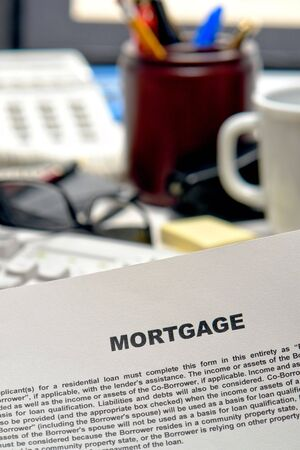 Real estate mortgage loan contract document on busy bank lender desk in lending agent office (fictitious document) Stock Photo - 6381538