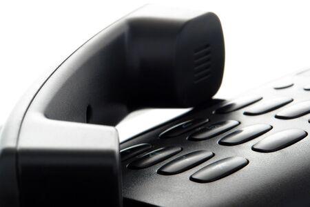 Black phone handset resting on telephone keypad