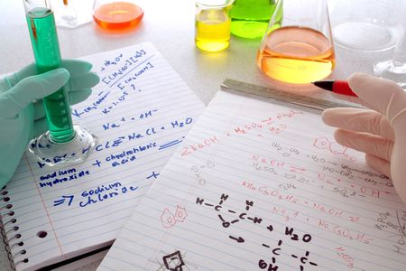 Two scientist comparing chemistry formulas on hand written notepads in a science research lab (fictitious notes) Stock Photo