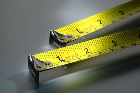 Two self retracting construction tape measures illustrating the maxim measure twice cut once