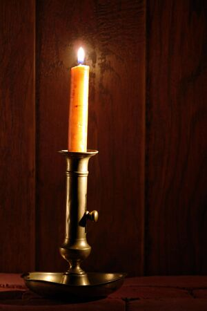 Antique brass candlestick with burning candle in an old historic house