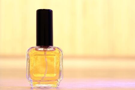 Glass spray bottle of yellow color perfume with tall black cap