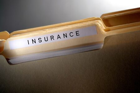 File folder in a stack with the printed word insurance on tab
