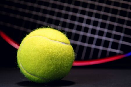 Yellow tennis ball and racket in background