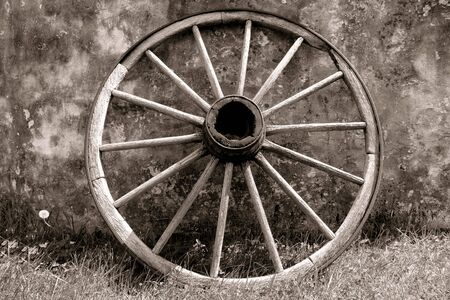 wagons: Old Conestoga wagon wood wheel against an old wall