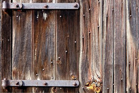 Weathered old wood barn door with vintage iron hinges photo