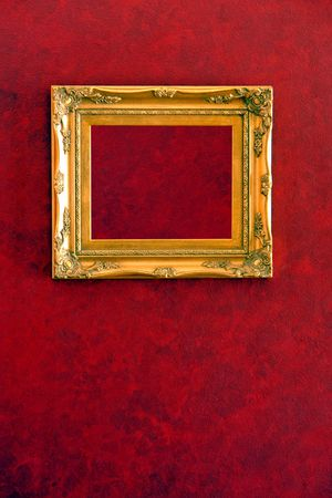 Empty gilded gold frame hanging on hand painted red wall