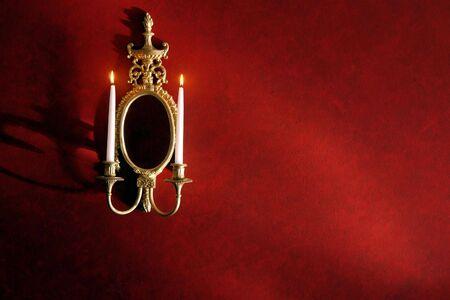 wall sconce: Oro envejecido dorado candelero de espejo de candelabros de pared con la grabaci�n de velas de cera en un muro rojo en una casa hist�rica