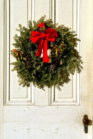 Decorative Christmas wreath with red bow and pine cones on old antique house door photo