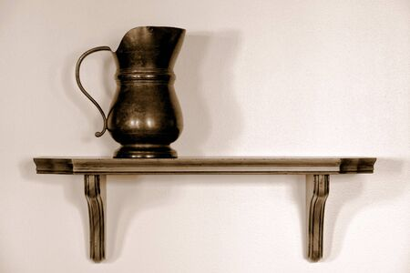 Old antique pewter serving pitcher on a wood shelf in a historic home