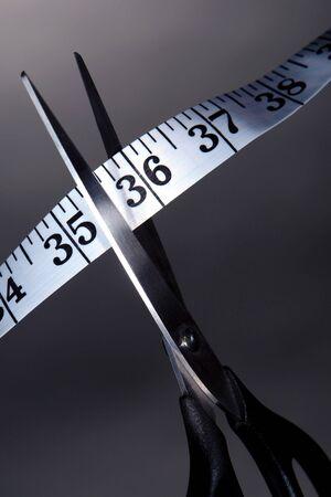 切断・切削ウエスト ダイエットをする隠喩としてリボン テープ メジャーをスライス鋭いはさみ