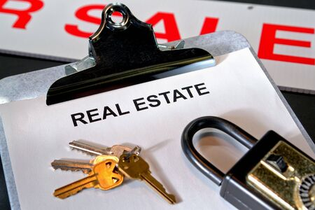 lockbox: Paperwork with the words real estate on a clipboard with set of house keys and lockbox