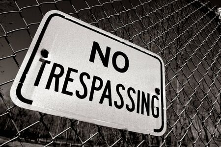 no entry sign: Posted no trespassing warning sign on chain link wire fence Stock Photo