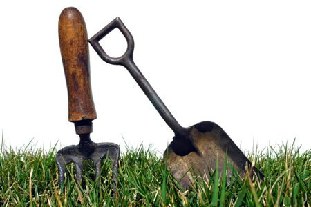 Antique gardening tools shovel and spading fork in grass over white