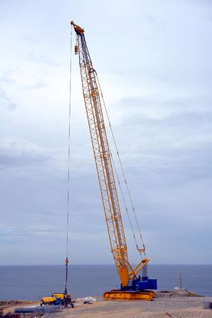 Crawler type derrick crane with outriggers and lattices boom fitted with a jib on a construction site