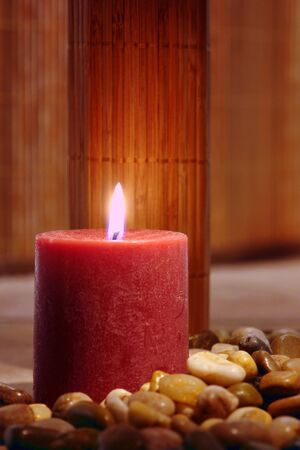 Aromatherapy candle softly glowing and burning on a bed of pebbles in a spa