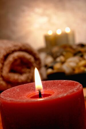 Aromatherapy candle softly glowing and burning with towel in a spa