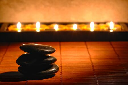 Polished black massage stone kern on bamboo mat with candles in a spa